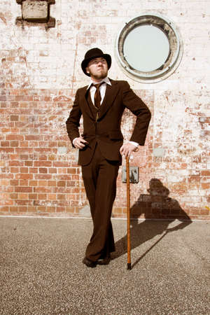 guy with walking stick: Young Retro Gentleman In Suit, Bowler Hat And Walking Stick Wth Brick Wall Background