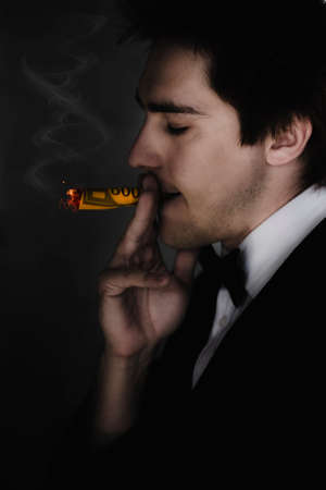 unsustainable: Business Man Standing In The Darkness Smoking And Burning A Hole In A 500 Dollar Bill In A Sign Of Unsustainable Excess Consumption Disorder Defined As A Societal Addiction Stock Photo