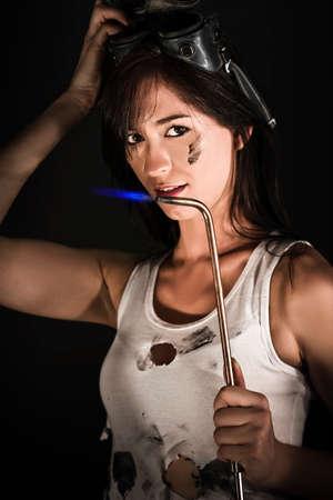 soldador: Oscuro retrato de una mujer joven morena atractiva en una tapa manchado de aceite y gafas de la celebración de un soplete quema en un concepto de chapista Foto de archivo