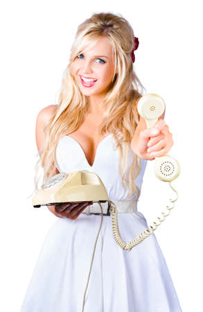 corded: Pretty blonde young woman in white dress with old fashion corded telephone