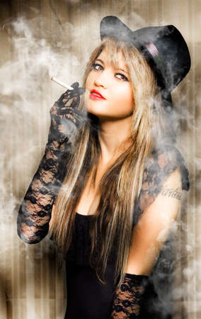 allurement: beautiful vintage girl smoking cigarette with pretty smile in a creative pinup style portrait Stock Photo