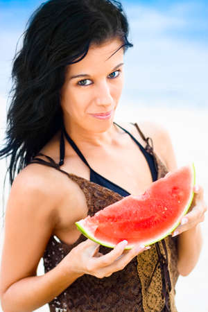 contentedness: Attractive Bikini Woman Holding A Slice Of Pink Juicy Watermelon Smiling With Expression Of Contentedness And Happiness As If She Loves The Watermelon