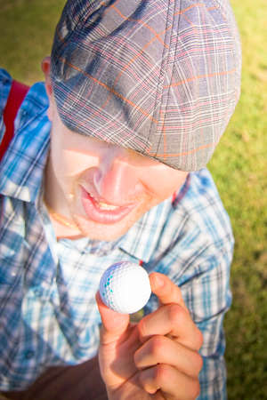 balmy: Balmy And Nutty Golfer Man Holds Up His Gold Ball During Play On The Golfing Field In A Madcap Sports Mad Picture Stock Photo