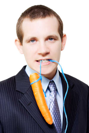dangling: Handsome young business person dangling a carrot on a string from his mouth concpetual of offering an incentive bonus as a reward for harder work