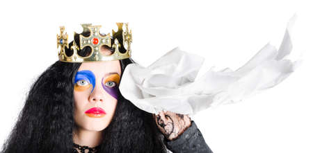 teary: Sad queen with face makeup and crown holding handkerchief, white background Stock Photo