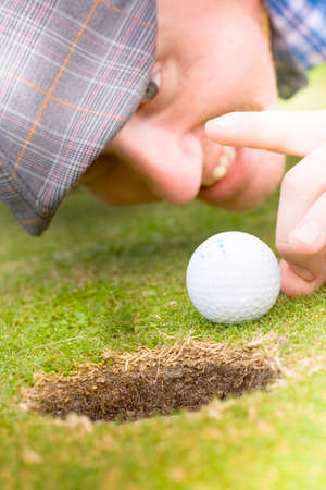 squatting down: Golfer Man Wearing A Flat Cap Pulls A Funny Smug Expression When Squatting Down To Give A Golf Ball A Flick Into The Hole In A Sporting Cheat Concept Stock Photo
