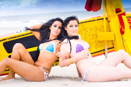 babes: Two Surfer Beach Babes Lie Back To Back In Bikini While On A Relaxing Surfing Beach Holiday, Yellow Surf Ski In Background Stock Photo