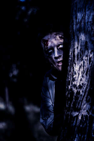 the watcher: Dark evil portrait of a creepy zombie man peering from behind trees in a night forest. The watcher