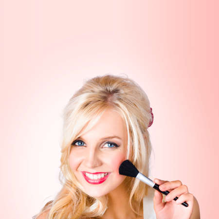 guile: Delightful female make-up model using blush powder makeup brush when demonstrating the art of Blushing. Pink Background Stock Photo