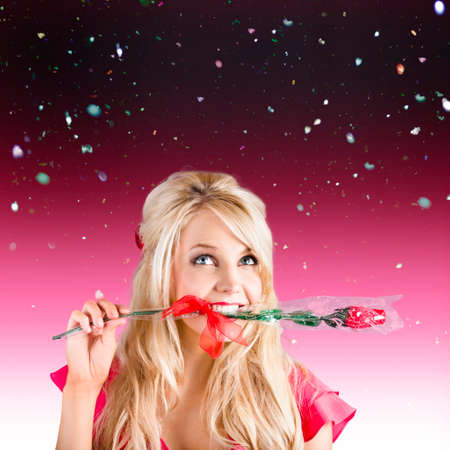 assignation: Romantic young female holding rose in mouth while looking up to falling confetti copyspace. Valentines day concept Stock Photo