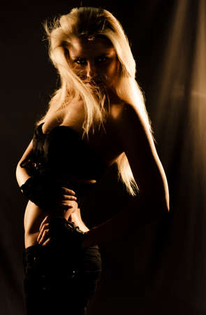 tetona: Encantador, carismático y bailarina bella rubia en movimiento misteriosamente en las profundas sombras de oscuridad durante un elegante y atractivo de la danza de la mística