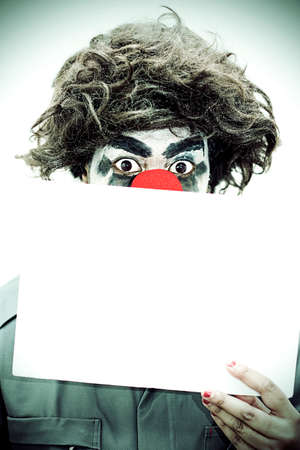 surprise party: Surprise Birthday Clown Peers Over A Blank Sign With A Look Of Wide Eye Shock In A Party Invitation Concept Stock Photo