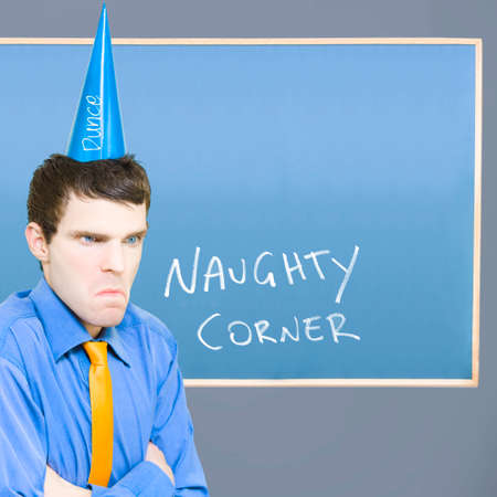 uneducated: Unhappy Businessman Sulking In The Naughty Corner While Wearing A Dunce Hat In A Depiction Of A Bad Business Decision