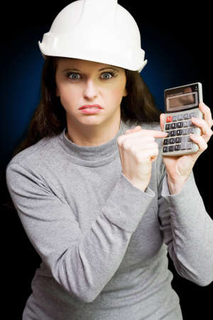 overrun: Furious under paid female manual labour worker wearing a hard hat and holding a calculator which she is striking in anger with her finger, conceptual for workers pay strike