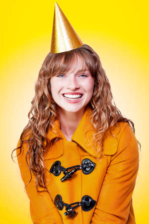 party hat: Laughing winter party girl wrapped up in a cheerful warm orange coat with a golden party hat on her head as she enjoys the celebrations on yellow