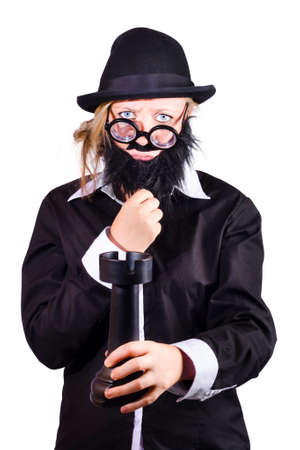 bespectacled: Funny bespectacled woman with black stick-on beard, mustache, homburg hat and jacket holding large Castle or rook chess piece isolated on white Stock Photo