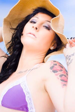 supercilious: Closeup Portrait Of A Tattooed Young And Pretty Woman In A Summer Bikini And Hat Standing With Head Tiled Back On A Sandy Beach In Blue Sky Paradise
