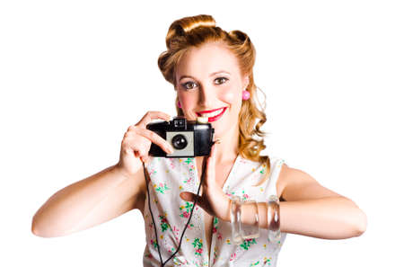 viewfinder vintage: Attractive smiling blond woman taking a picture with a black retro film camera on white background