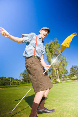 spontaneous expression: Golfer Man Grabs The Golf Hole Pole And Rides It Around The Golfing Green In Success After Celebrating A Successful Putt In Golf Victory Dance