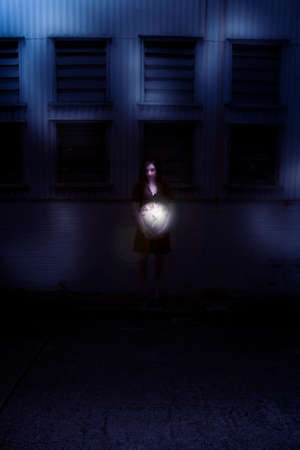 dimly: Woman Holding Clock Near A Building At Night In A Night Time Concept