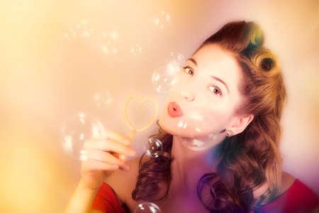 donna innamorata: Morbido ritratto romantico di una donna giovane e bella pin-up con i capelli stile retrò e perfetto make up che soffia bolle di compleanno attraverso il cuore di amore. Summer dreams