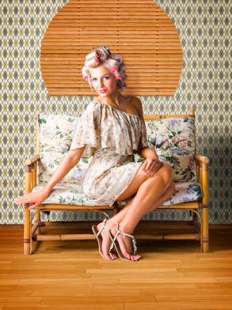 glamur: Sexy Fashion Photo Of Beautiful Girl Wearing Hair Rollers Sitting On A Vintage Floral Sofa In A Depiction Of Pinup Style Glamur Stock Photo