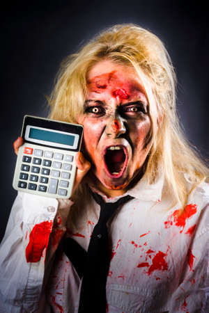 monstrous: Shocked dead finance accountant holding calculator when working out a monstrous tax debt . Return from the dead Stock Photo