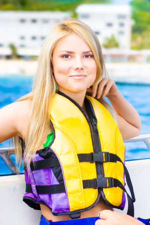 flotation: Beautiful blonde woman wearing a life jacket and relaxing against the rails on deck on a sightseeing boat tour Stock Photo