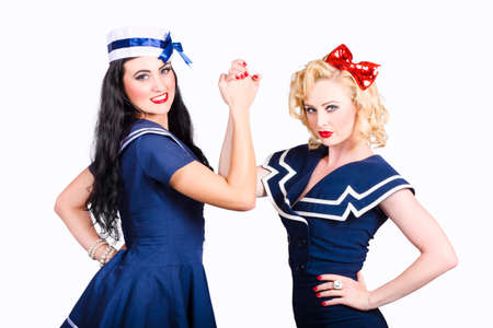 supremacy: Two beautiful sailor pinup girls arm wrestling in a battle for supremacy and victory. Competition and challenge