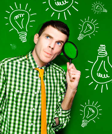 spy glass: Male Business Person Thinking With Spy Glass To Face In Front Of A Green Light Bulb Background In A Portrayal Of Discovery And Creative Ideas