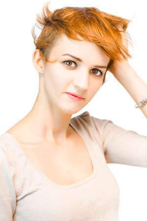 apprehension: Studio portrait of a beautiful redhead woman looking directly at the camera with a serious expression while running her hand through her short auburn hair Stock Photo