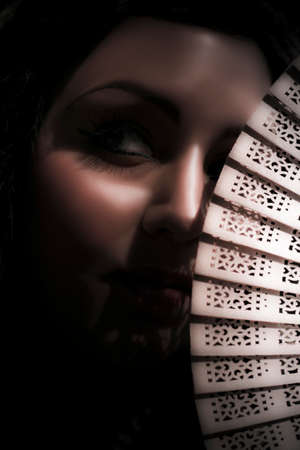 evocative: Dark And Mysterious Woman Veiled In Mystery And Obscurity Peers Out From The Shadows Of Darkness Behind The Blades Of A Hand Held Vintage Fan