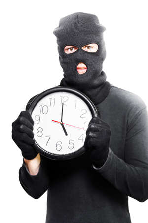 assailant: Male criminal in a black mask holding a stolen clock showing five oclock in knock off time conceptual isolated on white background