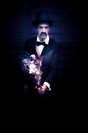 sympathy: Dim Portrait Of A Sad Young Man In Suit Holding A Small Bouquet Of Flowers Representing With Sympathy, Color Modified