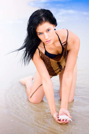 beach babe: Beach Babe With Black Hair Wearing Black Bikini Holding A Shell As She Kneels In The Shallow Ocean Water With Pretty Expression Stock Photo
