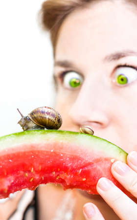 befuddled: Surprised Woman Finds Snails Slithering Along The Bottom Of Her Half Eaten Watermelon Stock Photo
