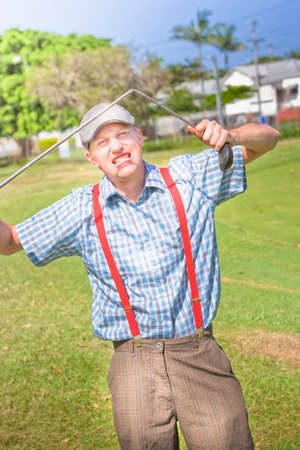 tantrum: Irritable Golfer Throws A Fit Of Rage On A Landscape Grassy Green Golf Course Breaking His Golfing Stick When Throwing A Golf Temper Tantrum Stock Photo