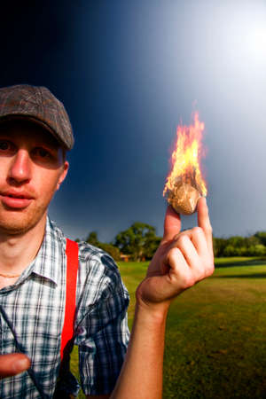 immersed: Golfer Man Holds A Scorching Golf Ball Immersed In Flames And Fire In A Golfing Representation Of Hot Sport Stock Photo