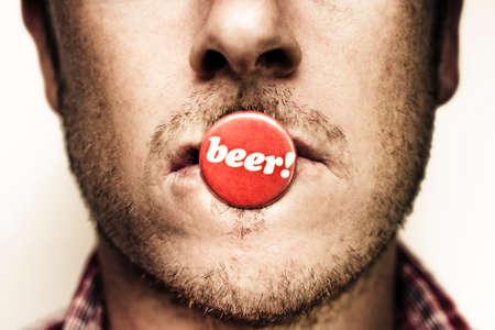 hombre tomando cerveza: grunge fotografía en la cara de un hombre joven sin afeitar con un botón de estaño o insignia que muestra la palabra cerveza en los labios de señalización su amor insaciable de cerveza