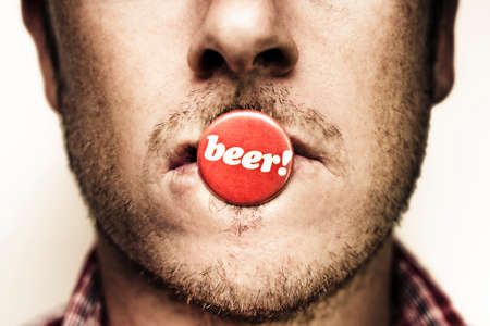 beer bottle: Grunge photograph on the face of a unshaven young man with a tin button or badge displaying the word Beer on his lips signalling his insatiable love of beer Stock Photo