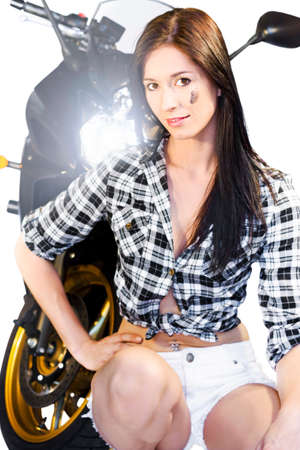 crouched: Pretty slender girl posing crouched in front of a motorbike with its headlight shining over her shoulder
