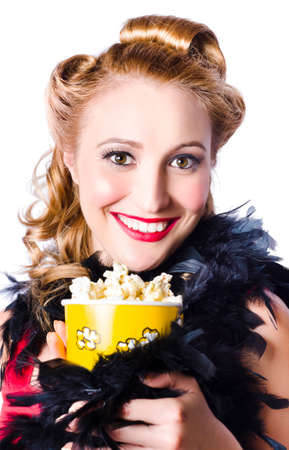 robo: Retrato de la atractiva atractiva que desgasta plumas mujer rubia se apoderó de vestido rojo que sostiene una caja de palomitas de maíz