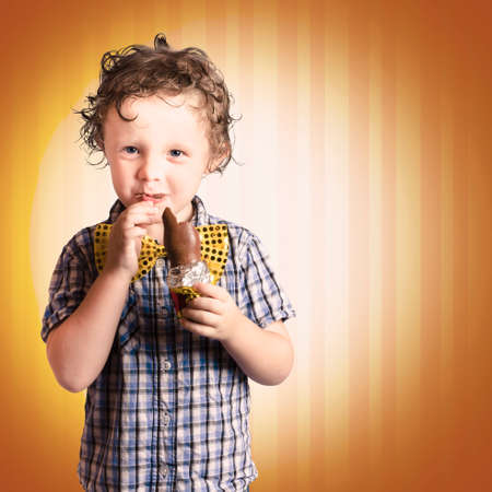devouring: Lovable Little Child Eating Chocolate Easter Bunny Present On Striped Brown Background Stock Photo