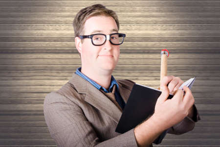 notations: Funny nerd businessman minuting massive business plan when writing with huge pencil in black note book. Wood blinds background Stock Photo