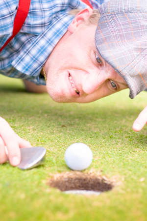 lunacy: A Frustrated Yet Funny Golfing Fanatical Man Points At His Golf Ball While Hurling A Barrage Of Insults In A Comical Image Representing Golf Lunacy Stock Photo