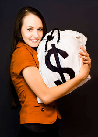 possessive: Smiling attractive woman holding on tightly to a large money bag full of dollars, studio portrait on black
