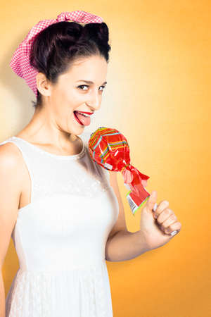 retro housewife: Silly portrait of a retro housewife craving sweet candy when holding a large lollypop. Confectionary pin ups