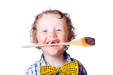 chocolaty: Happy young boy with chocolate covered wooden spoon in mouth, white background Stock Photo