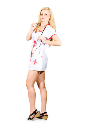 Blonde sexy nurse in short miniskirt unofrm and stethoscope posing sideways showing off her legs. Stock Photo