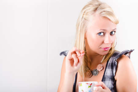 indulging: Beautiful Blond Girl Holding Teabag And Teacup When Indulging In A English Tea For Breakfast